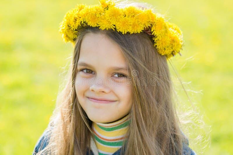 Porträt des glücklichen achtjährigen Mädchens mit einem Kranz des Löwenzahns auf ihrem Kopf, vor dem hintergrund einer Frühlingsr stockbild