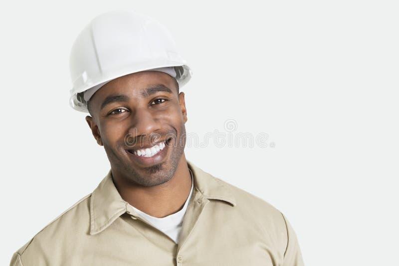 Porträt des glücklichen afrikanischen Baus vorbei mit Hardhat über grauem Hintergrund stockbild