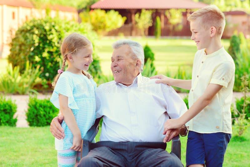 Porträt des glücklichen alten Großvaters und der netten Kinder stockbild