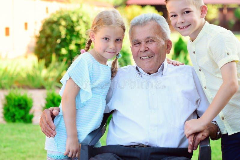 Porträt des glücklichen alten Großvaters und der netten Kinder stockfotos