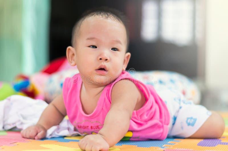 Porträt des glücklichen asiatischen Babys auf dem Bett stockbilder