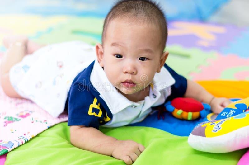 Porträt des glücklichen asiatischen Babys auf dem Bett lizenzfreies stockfoto