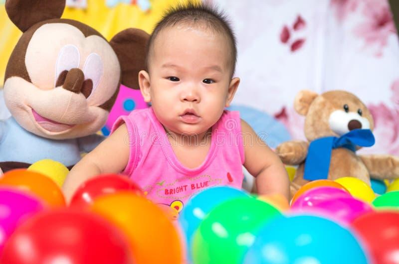 Porträt des glücklichen asiatischen Babys mit vielen Spielwaren lizenzfreie stockfotografie