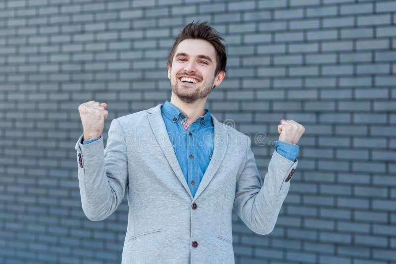 Porträt des glücklichen aufgeregten hübschen bärtigen Mannes in der zufälligen Art, die mit den Fäusten, dem toothy Lächeln und d lizenzfreie stockbilder