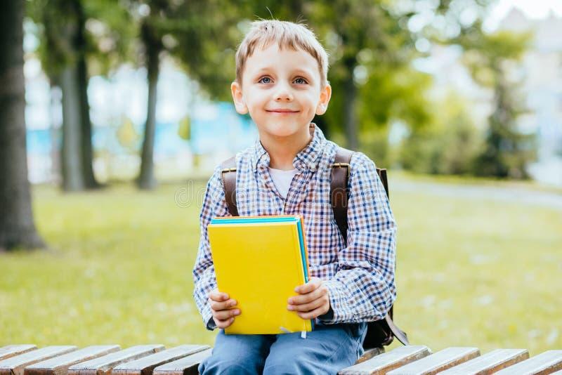 Porträt des glücklichen entzückenden Kleinkindjungen, der verschiedene bunte Bücher am ersten Tag zur Schule oder zur Kindertages lizenzfreie stockfotografie