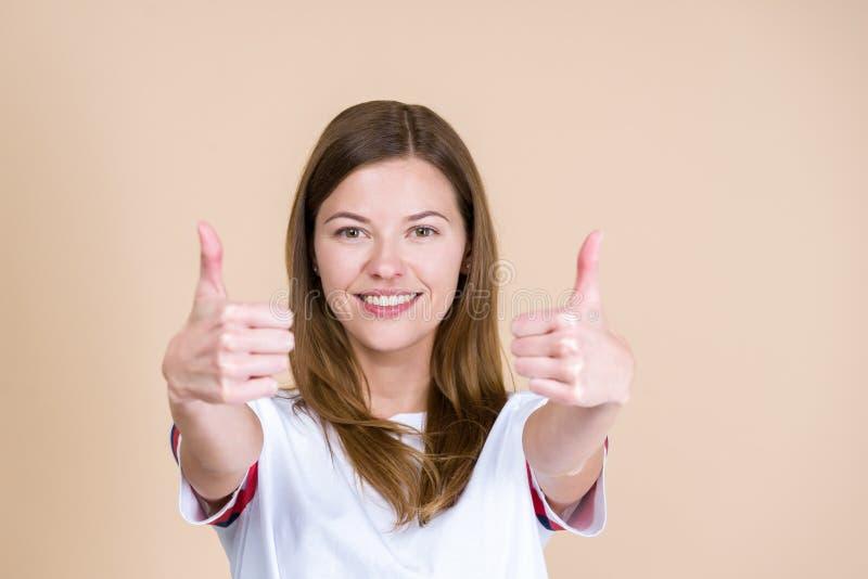 Porträt des glücklichen erwachsenen Mädchens, das Daumen lächelt, betrachtet Kamera und sich zeigt lizenzfreie stockfotografie