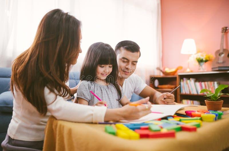Porträt des glücklichen Familientochtermädchens lernt Zeichnungsbuch zusammen mit Elternteil stockbild