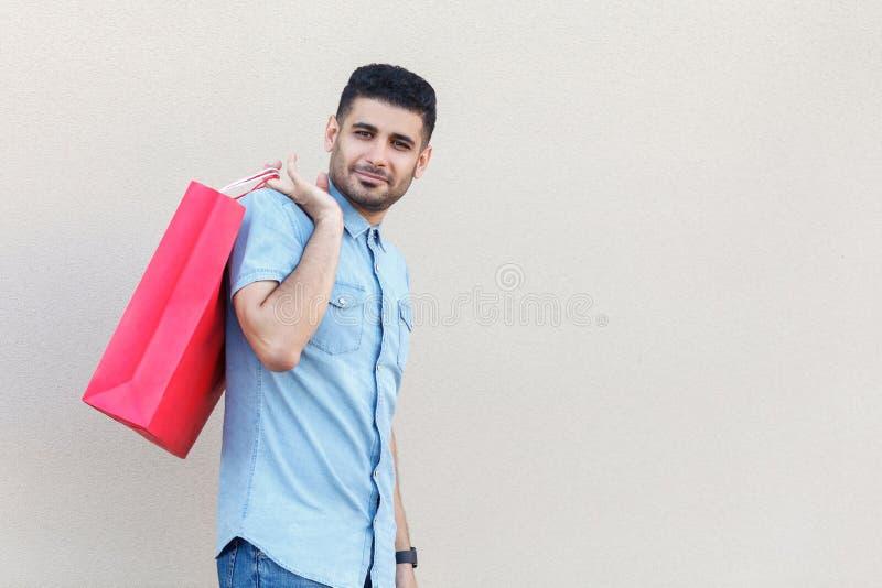 Portr?t des gl?cklichen frohen h?bschen jungen b?rtigen Mannes in der blauen Hemdstellung, rote Einkaufstasche oder Geschenk halt stockfotografie