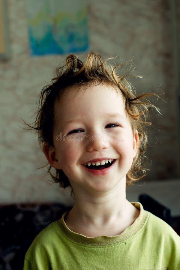 Porträt des glücklichen frohen schönen kleinen Jungen mit dem hellen Haar, große Frisur Er lacht und lächelt lizenzfreies stockfoto