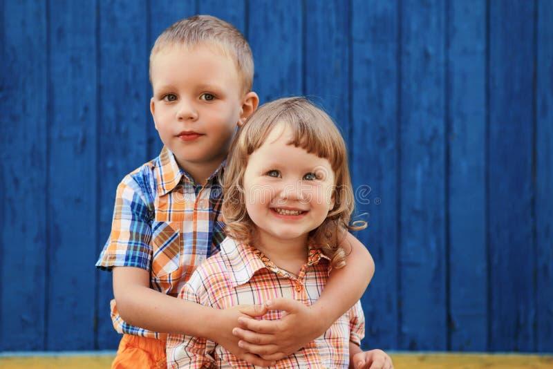 Porträt des glücklichen frohen schönen kleinen Jungen und des Mädchens gegen t stockfotografie