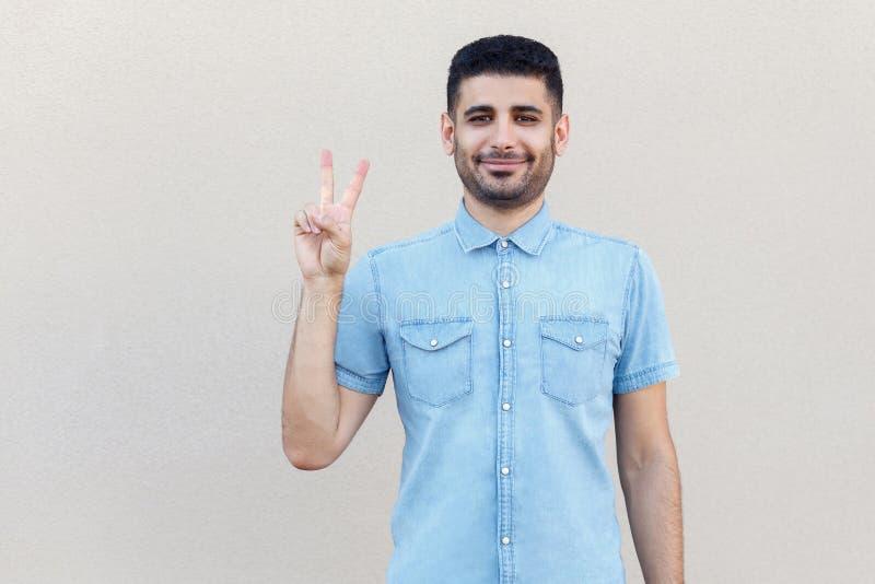 Porträt des glücklichen hübschen jungen bärtigen Mannes in der blauen Hemdstellung mit Sieg oder Friedensgestenhände und Betracht stockfoto