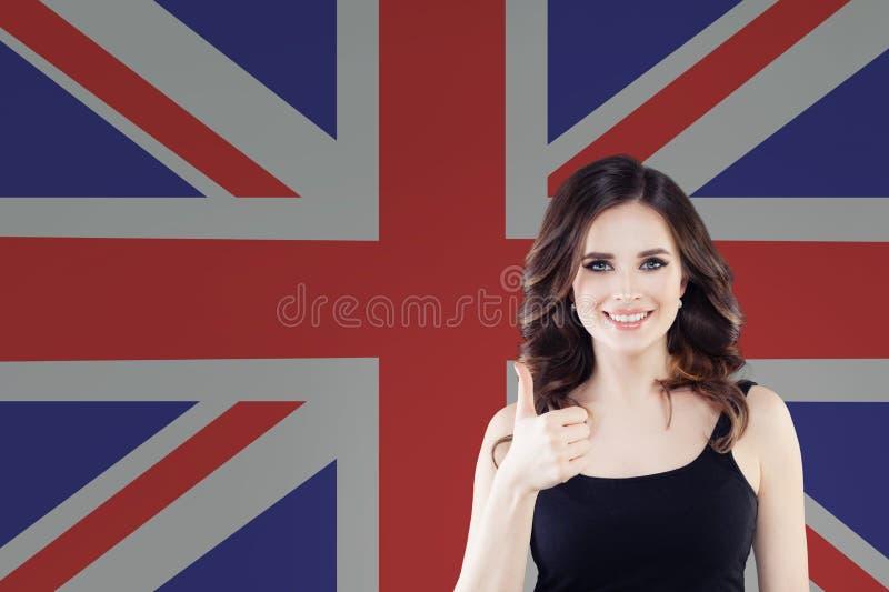 Porträt des glücklichen hübschen Mädchens mit dem Daumen oben auf dem BRITISCHEN Flaggenhintergrund Junge Frau, die englische Spr stockbilder
