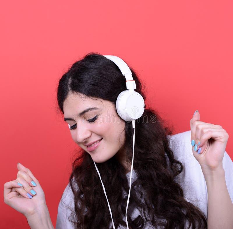 Porträt des glücklichen jugendlich Mädchentanzens und der hörenden Musik gegen stockbild