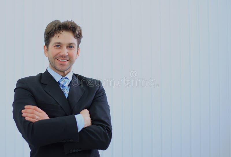 Porträt des glücklichen jungen Geschäftsmannes im Büro lizenzfreie stockfotografie