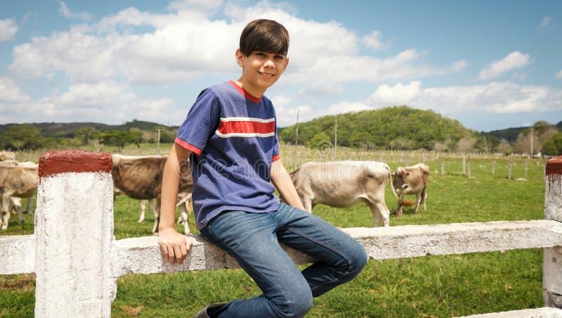 Porträt des glücklichen Jungen im Bauernhof mit Kühen in der Ranch lizenzfreie stockfotos
