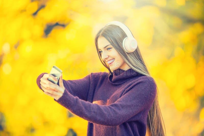 Porträt des glücklichen jungen Mädchens mit Kopfhörern und Smartphone im Herbst parken hörende Musik oder machen selfie lizenzfreie stockbilder