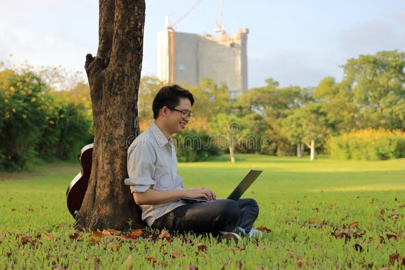 Porträt des glücklichen jungen Mannes lächelt mit einer Laptop-Computer im Stadtpark stockbilder