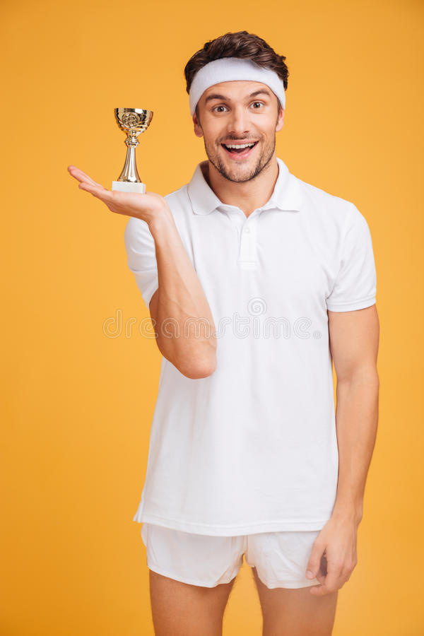 Porträt des glücklichen jungen Sportlers, der Trophäenschale hält stockfotos