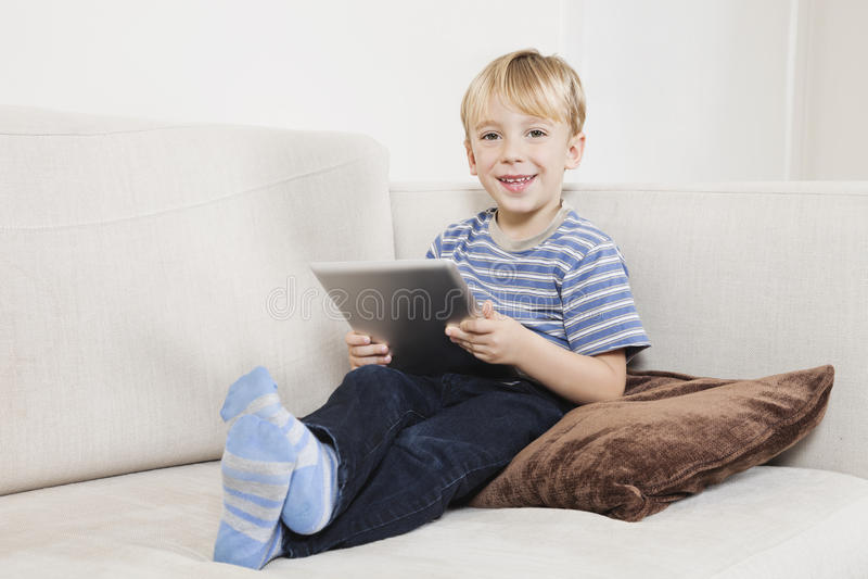 Porträt des glücklichen Jungen Tablet-PC auf Sofa halten lizenzfreies stockbild