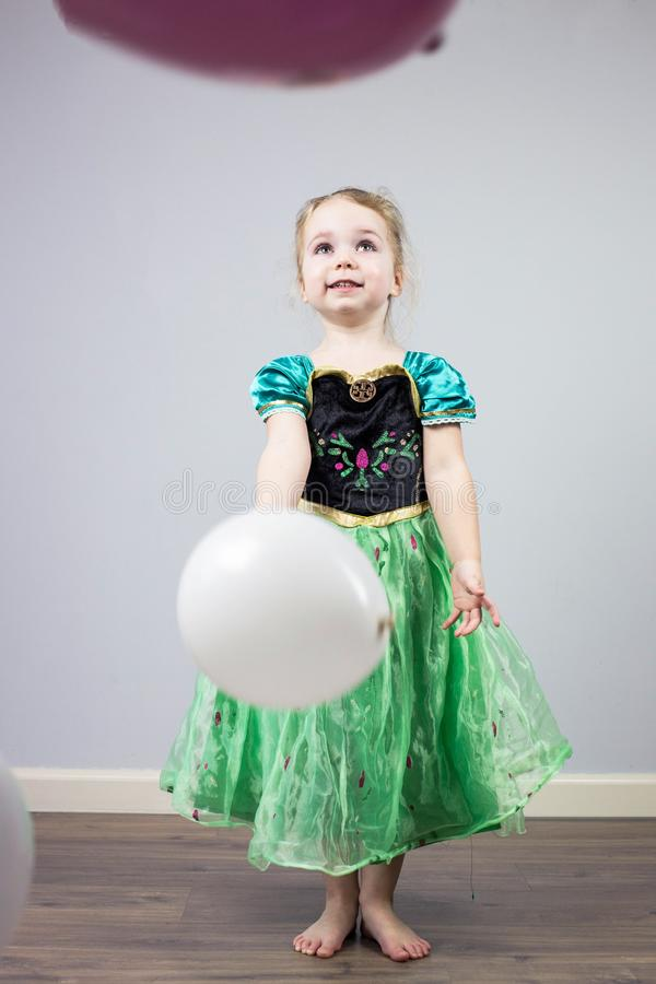 Porträt des glücklichen Kindes, spielerisch mit den Rosa- und weißenballonen und einem Prinzessinkleid lizenzfreie stockbilder