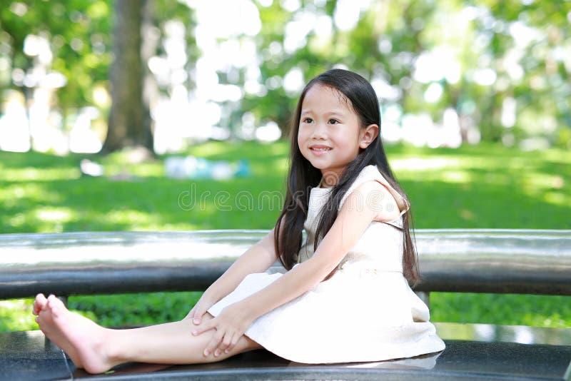Porträt des glücklichen kleinen asiatischen Kindermädchens, das auf Bank im sonnigen grünen Park sitzt stockfotografie