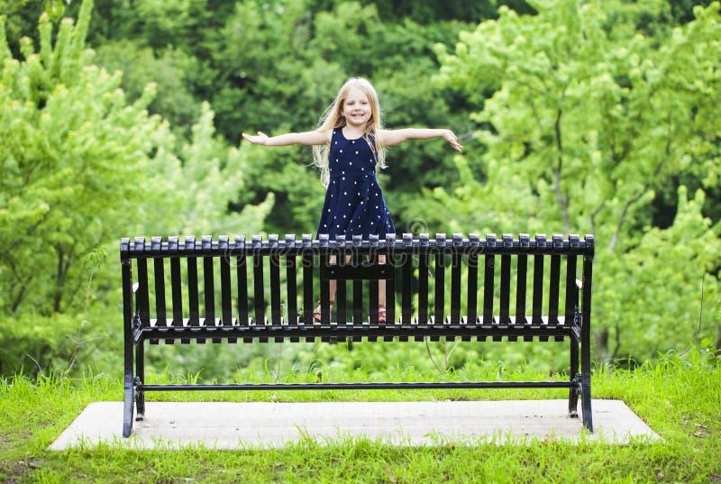 Porträt des glücklichen kleinen Mädchens, das auf Metallbank im Park steht stockfotografie