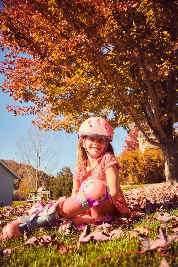 Porträt des glücklichen kleinen Mädchens in den Rollschuhen stockbild