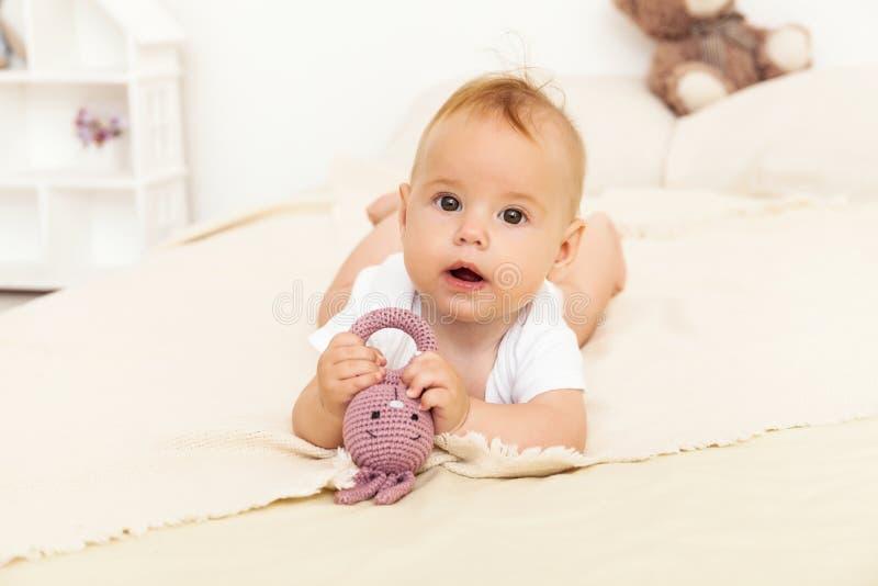 Porträt des glücklichen Lächelnbabys, das auf dem Bett sich entspannt stockbild
