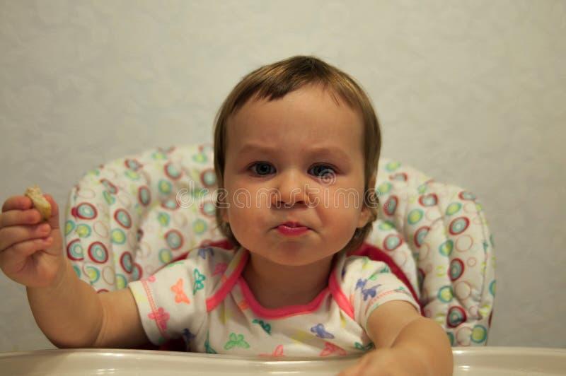 Porträt des glücklichen lächelnden Babys, das Plätzchen im Hochstuhl isst stockbilder