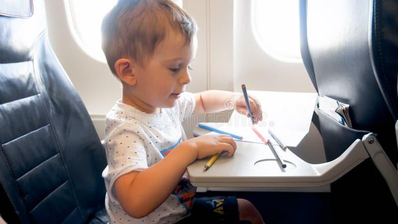 Porträt des glücklichen lächelnden Fliegens des kleinen Jungen im Flugzeug und in der Zeichnung mit Bleistiften lizenzfreie stockbilder