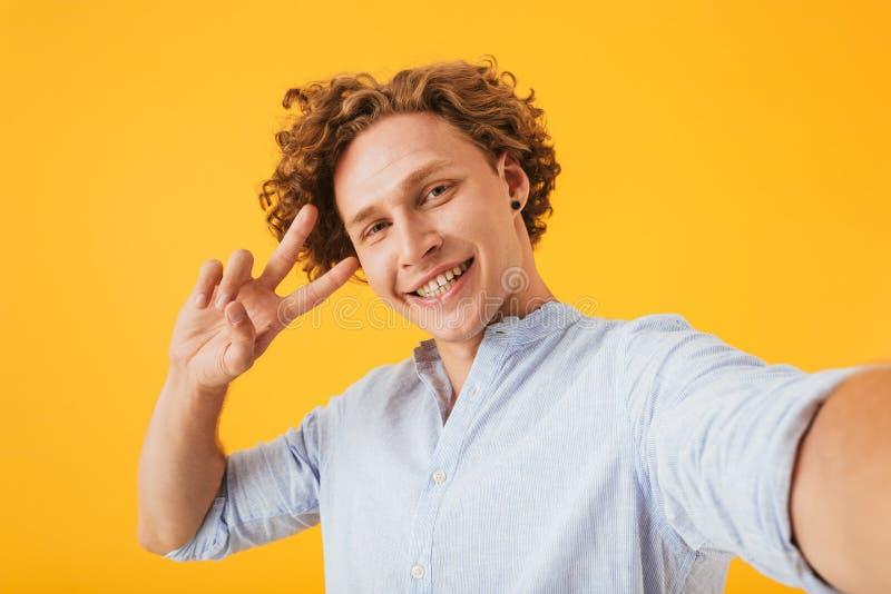 Porträt des glücklichen lächelnden Kerls 20s, der selfie Foto und showin nimmt lizenzfreies stockbild