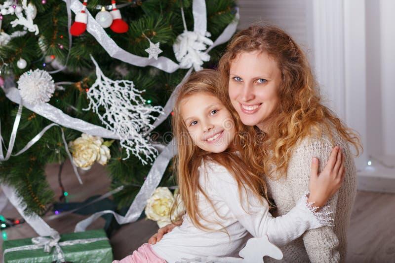 Porträt des glücklichen lächelnden kleinen Mädchens mit der Mutter, die nahe C sitzt stockfoto