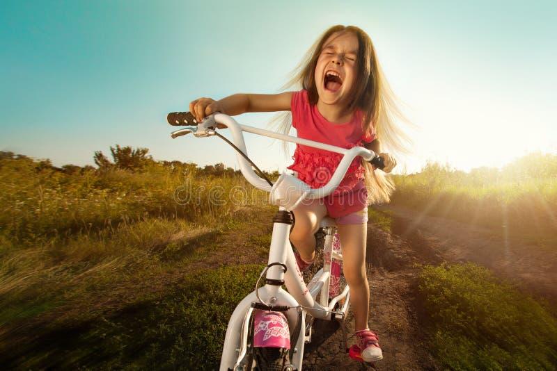Porträt des glücklichen lustigen Mädchens auf Fahrrad lizenzfreies stockbild