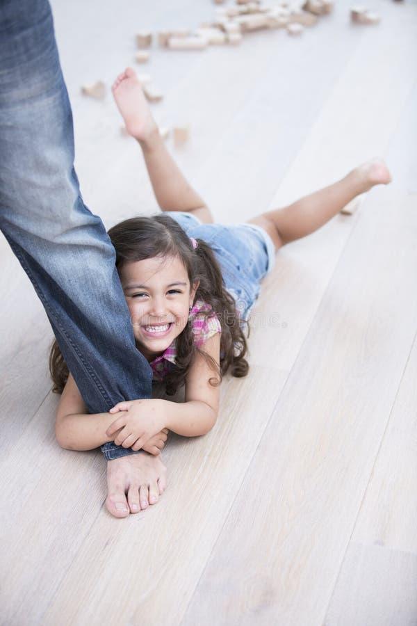 Porträt des glücklichen Mädchens, das vom Vater auf Massivholzboden geschleppt wird lizenzfreie stockfotografie