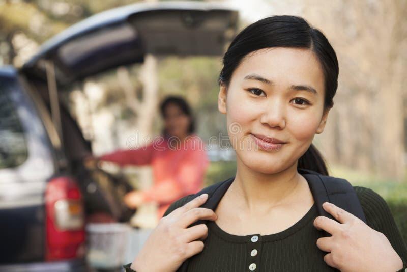 Porträt des glücklichen Mädchens vor Auto auf Collegecampus stockbild