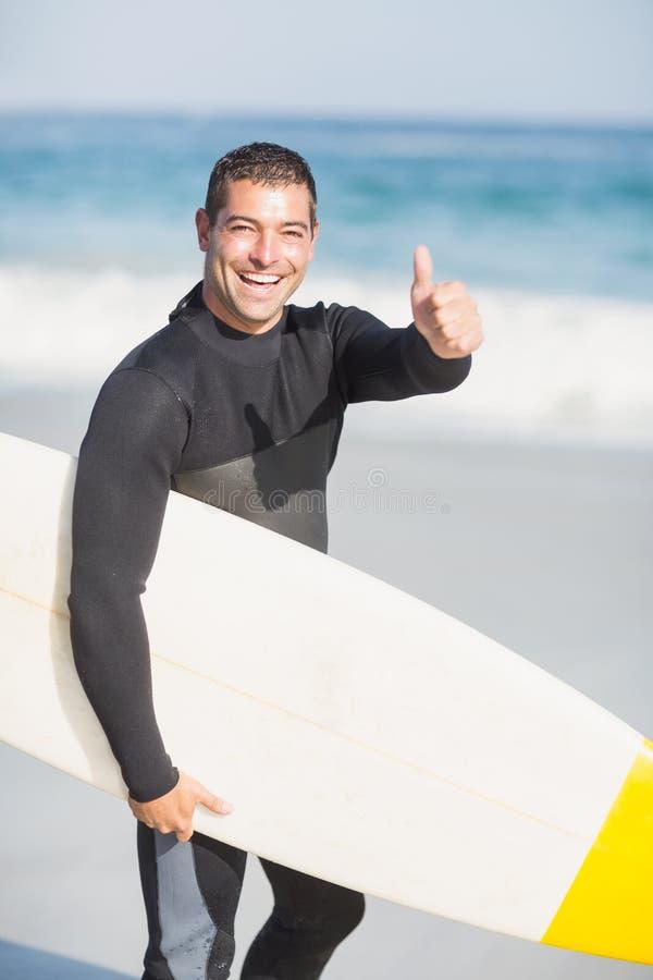 Porträt des glücklichen Mannes ein Surfbrett auf dem Strand halten stockfotos