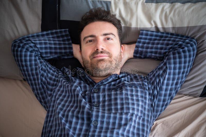 Porträt des glücklichen Mannes in seinem Bett morgens stockbild