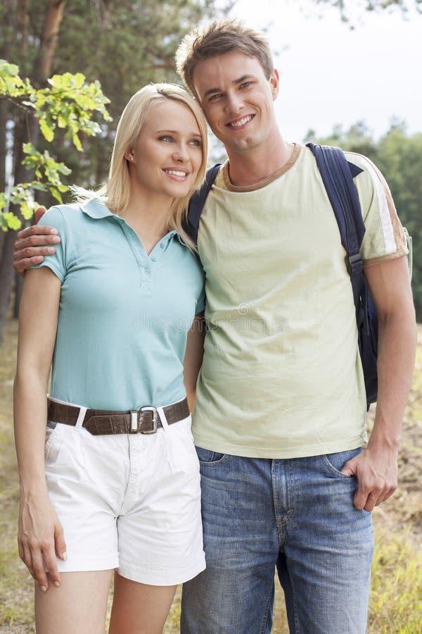 Porträt des glücklichen Mannes stehend mit Frau beim Wandern im Wald lizenzfreie stockfotos