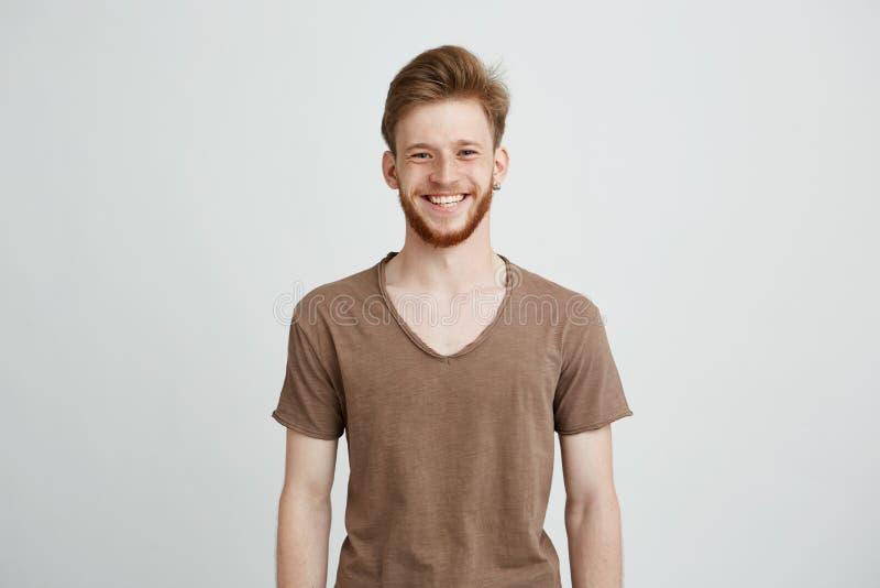 Porträt des glücklichen netten jungen Mannes mit Bart lächelnd, Kamera über weißem Hintergrund betrachtend lizenzfreie stockfotografie
