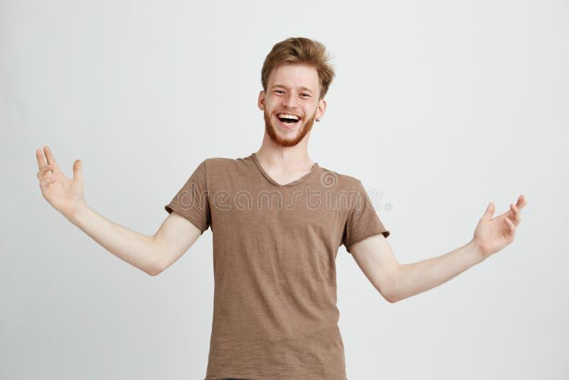 Porträt des glücklichen netten positiven lachenden freuenden Gestikulierens des jungen Mannes, Kamera über weißem Hintergrund bet lizenzfreie stockbilder