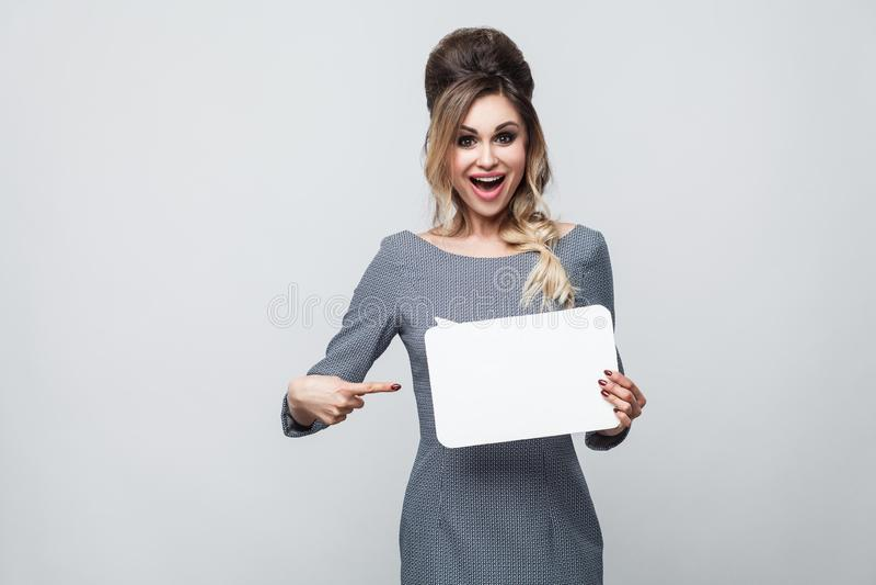 Porträt des glücklichen netten schönen modernen jungen Mädchens im grauen Kleid, das Finger steht, hält und zeigt, um Wolke zu sa lizenzfreies stockbild