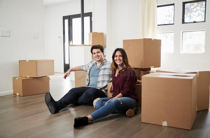 Porträt des glücklichen Paars sitzend auf dem Boden umgeben durch Kästen im neuen Haus an beweglichem Tag stockbild