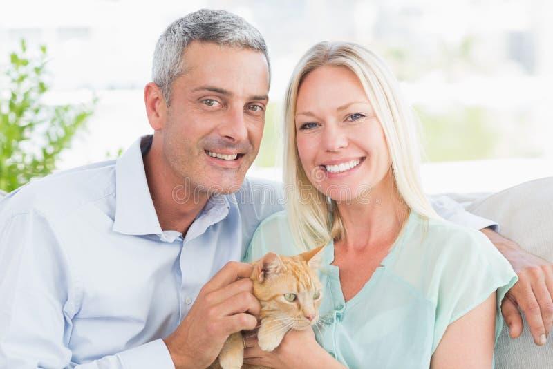 Porträt des glücklichen Paars spielend mit Katze lizenzfreie stockfotos