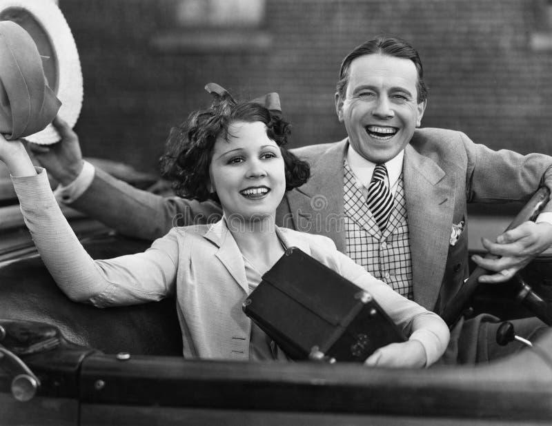 Porträt des glücklichen Paars wellenartig bewegend in Auto stockfoto