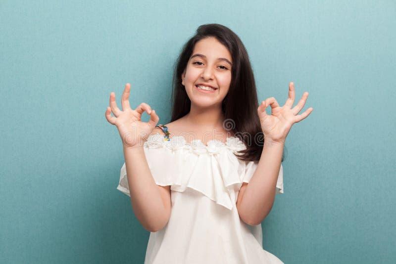 Porträt des glücklichen schönen brunette jungen Mädchens mit dem langen geraden Haar in der weißen Kleiderstellung mit O.K.zeiche lizenzfreies stockbild