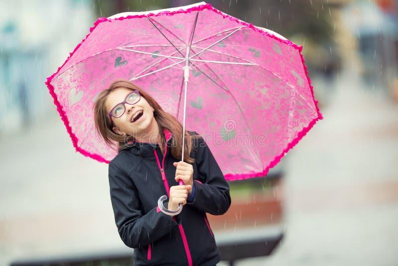 Porträt des glücklichen schönen jungen jugendlichen Mädchens mit rosa Regenschirm unter Regen stockfotos