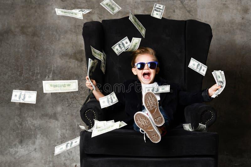 Porträt des glücklichen schreienden selbstbewussten reichen Kinderjungenmillionärs, der im Luxuslehnsessel und in werfendem Geldd stockfotos