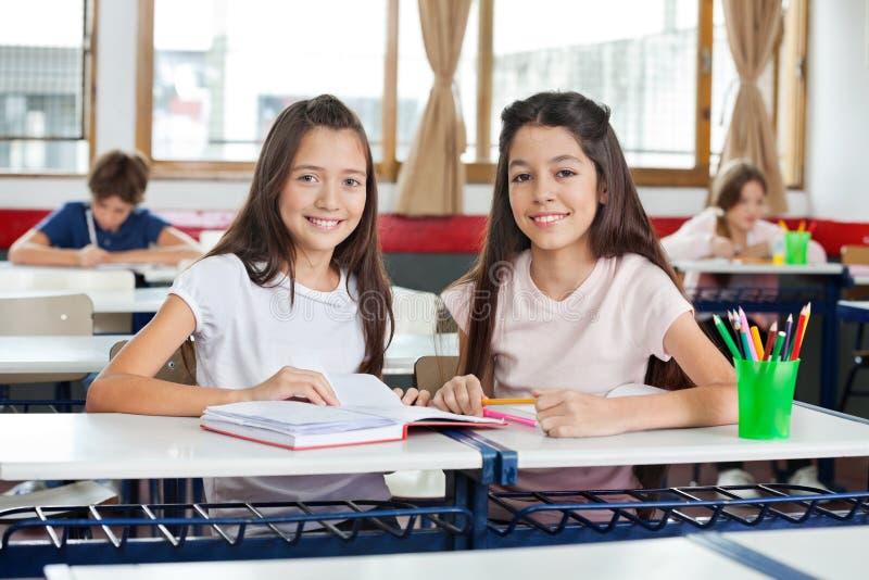 Porträt des glücklichen Schulmädchen-Sitzens stockbilder