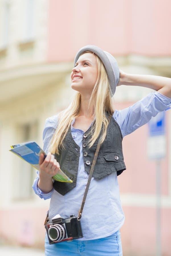 Porträt des glücklichen touristischen Mädchens mit Karte auf Stadtstraße lizenzfreie stockbilder