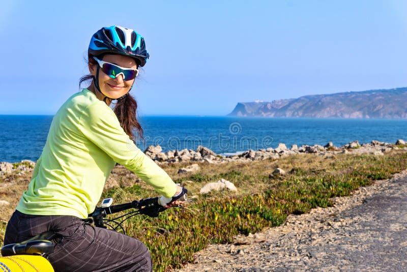 Porträt des glücklichen touristischen Radfahrers auf der Straße entlang dem Ozeanufer, das zurück der Kamera und dem Lächeln betr stockfotos